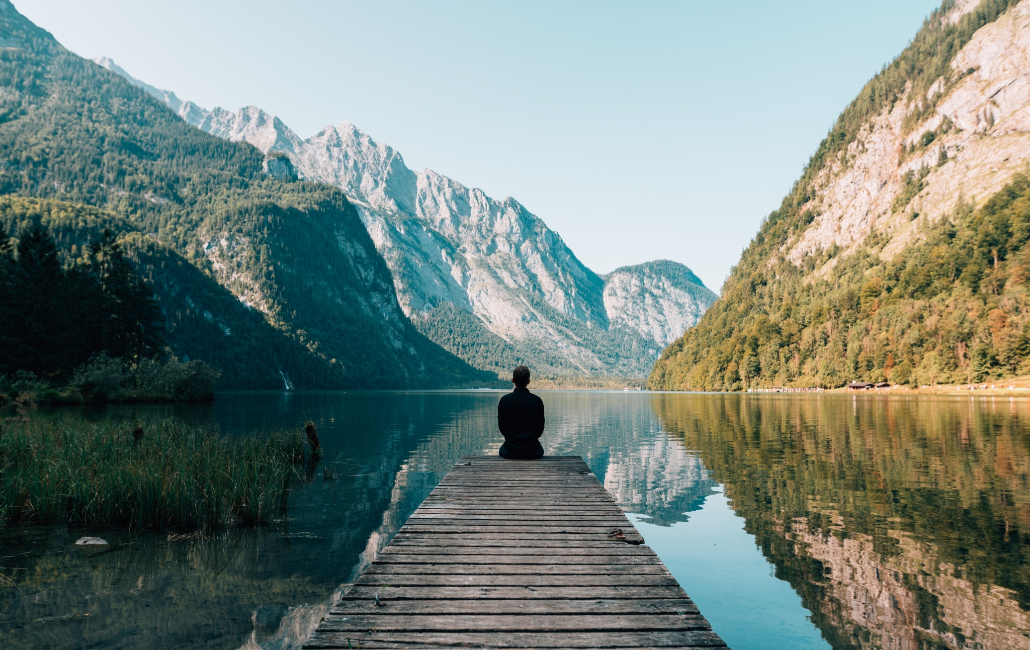 Man sitting on a pier amongst a lake and mountains