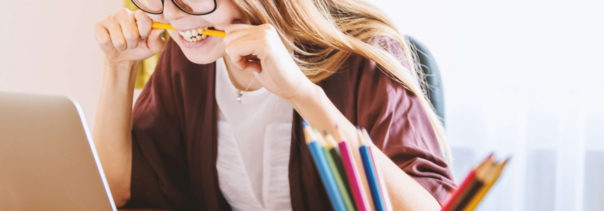Stressed woman chewing on pencil doing test